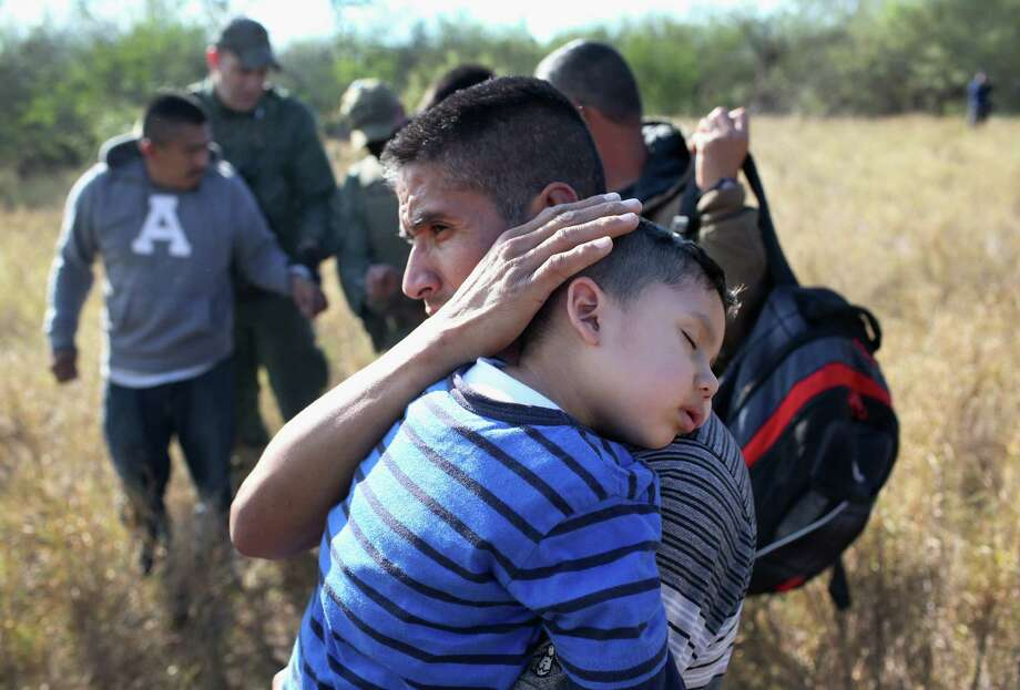 """A father holds his sleeping son, 3, after they and others are detained by Border Patrol agents near Rio Grande City. Readers criticize government officials for what they term the political correctness that leads them to want to call such individuals """"undocumented immigrants"""" instead of """"illegal aliens"""". Photo: John Moore /Getty Images / 2015 Getty Images"""