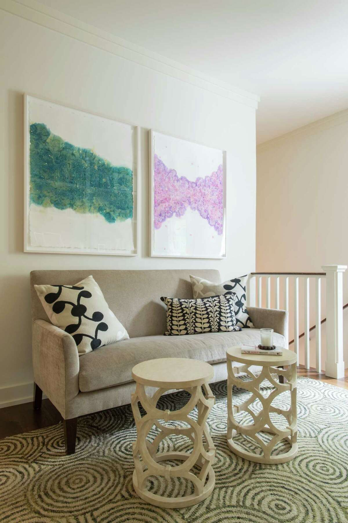 The second floor of this Heights home has an open, broad landing. Designer Linda Eyles put in a loveseat and two small tables, then added color with pieces of art on the walls.