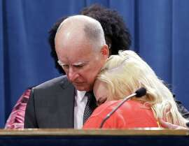 California Gov. Jerry Brown is hugged by Holly Diaz, a Burger King employee who praised Brown's announcement of proposed legislation to increase the state's minimum wage to $15 per hour by 2022, during a news conference in Sacramento, Calif. Monday March 28, 2016. If approved by the Legislature, California would be the first state to raise the minimum wage to $15.