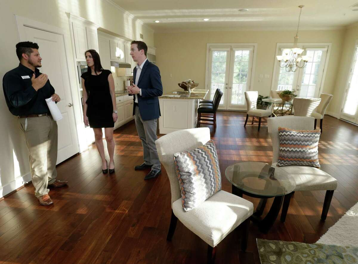 Joseph Delos Reyes, left, an agent with Better Homes and Gardens Real Estate Gary Greene shows Stephanie LeBlanc and Alex Dale a unit at Oasis Pointe Condominiums on Lake Woodlands Monday, March 28, 2016, in The Woodlands.