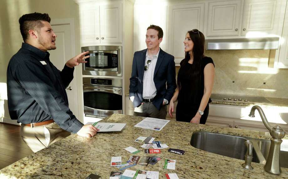 Joseph Delos Reyes, left, an agent with Better Homes and Gardens Real Estate Gary Greene shows Alex Dale and Stephanie LeBlanc a unit at Oasis Pointe Condominiums on Lake Woodlands Monday, March 28, 2016, in The Woodlands. Photo: Melissa Phillip, Houston Chronicle / © 2016 Houston Chronicle
