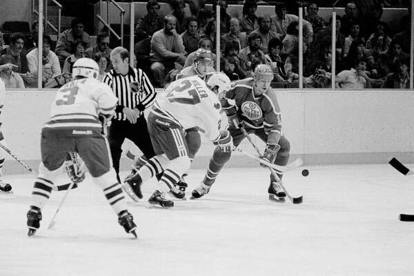 Warren Miller of the Hartford Whalers, left, and Mark Messier of the Edmonton Oilers, right, battle for the puck in the first period of the Whalers-Oilers NHL game in Hartford, Conn., Nov. 11, 1981. Miller was able to pick up the puck and take it down the ice for Hartford on the play.