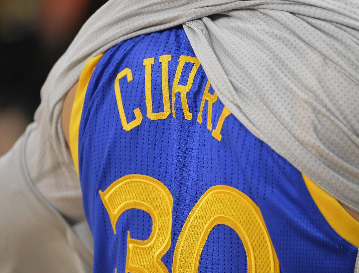 FILE-- Golden State Warriors guard Stephen Curry removes his warm-up jersey before an NBA basketball game against the San Antonio Spurs, Saturday, March 19, 2016, in San Antonio. Warriors point guard Stephen Curry has dethroned Kobe Bryant for China's best-selling jersey.