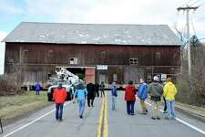 Spectators gather to watch as workers with Wolfe House and Building Movers move the 1898 Hilton Barn at LeVie Farm across Maple Avenue on Tuesday, March 29, 2016, in New Scotland, N.Y.  The post-and-beam barn is 120 feet long, 60 feet tall and 60 feet wide.  The barn was built by Voorheesville craftsman and timber framer Frank Osterhout.  The cost of moving the barn is approximately $150,000, which is being funded by $25,000 from the town and $50,000 from the county, with the hope that a State grant will cover the remaining costs.   (Paul Buckowski / Times Union)