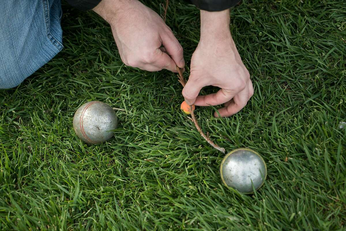 Charles Matteo determines the winner in a game of Petanque at Library Park in Lakeport, Calif. on Sunday, March 27, 2016. Lakeport offers visitors restaurants, entertainment and lakeside views.