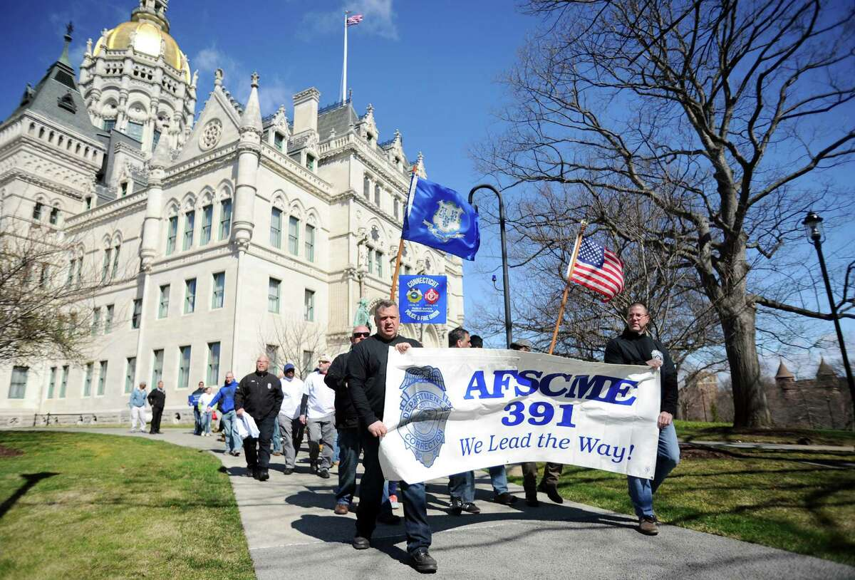 Hundreds of unionized state employees joined together outside of the Capitol to underscore how potential layoffs will affect Connecticut's quality of life on Tuesday, March 29, 2016 in Hartford, Conn.