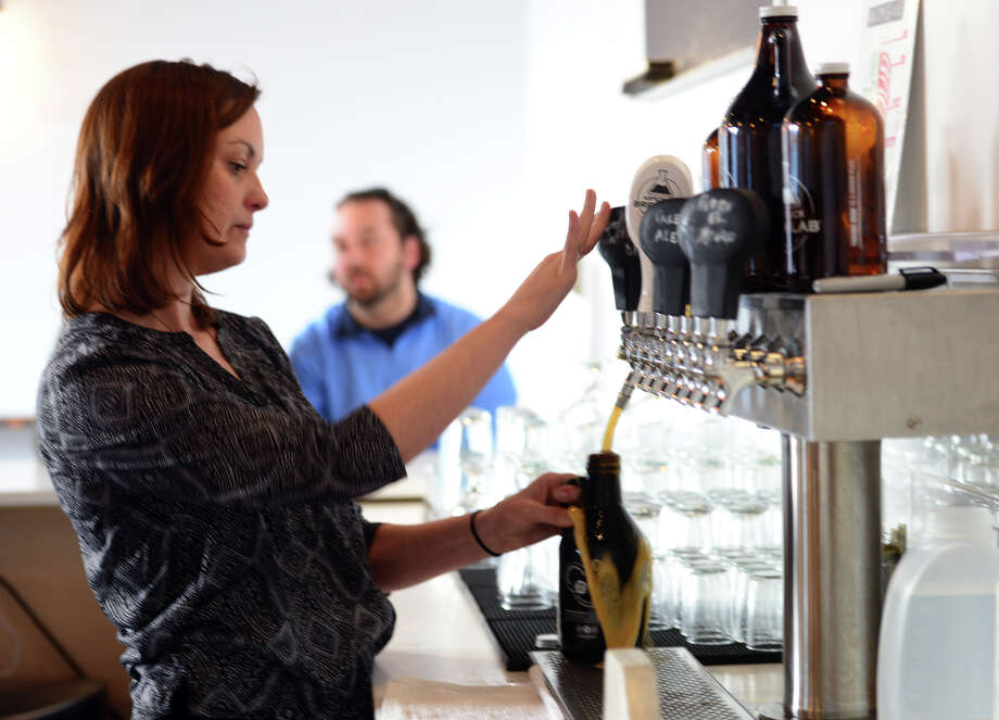 Aspetuck Brew Lab beer tender Ruth Buskey refills a growler for a customer at the new micro brewery on Fairfield Avenue in Bridgeport, Conn., on Friday March 18, 2016. This is the first brewery to be open in the city in over 70 years. Photo: Christian Abraham / Hearst Connecticut Media / Connecticut Post