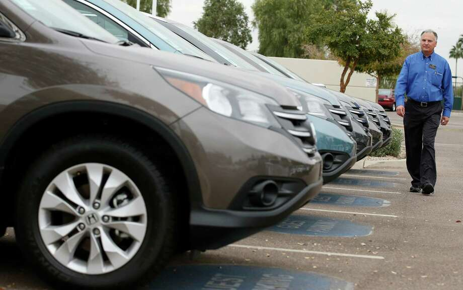 FILE - In this Tuesday, Dec. 2, 2014, file photo, Mike Johnson, a sales manager at a local Honda car dealership, walks past a row of Honda CRVs in Tempe, Ariz. If you're in the market for a Japanese car, March is a good time to buy. Unlike U.S., European and Korean automakers, which end their financial year on Dec. 31, Japanese companies like Toyota Motor Corp. and Honda Motor Co. close their books on March 31. (AP Photo/Ross D. Franklin, File) ORG XMIT: NYBZ383 Photo: Ross D. Franklin / AP