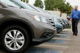 FILE - In this Tuesday, Dec. 2, 2014, file photo, Mike Johnson, a sales manager at a local Honda car dealership, walks past a row of Honda CRVs in Tempe, Ariz. If you're in the market for a Japanese car, March is a good time to buy. Unlike U.S., European and Korean automakers, which end their financial year on Dec. 31, Japanese companies like Toyota Motor Corp. and Honda Motor Co. close their books on March 31. (AP Photo/Ross D. Franklin, File) ORG XMIT: NYBZ383