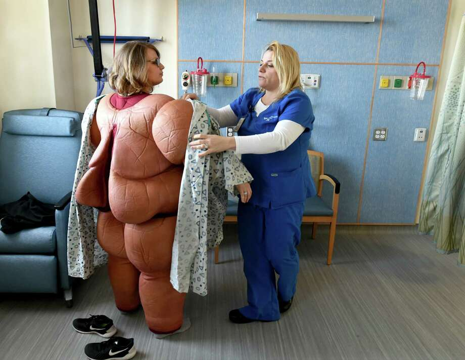 FILE - In this Friday, Feb. 12, 2016, file photo, nurse Brittany Boebert, left, is assisted by nurse Bethany Mulone, a bariatric educator, in trying on a bariatric patient simulation suit used for training at the dedicated Bariatric Surgery Unit on the Saint Raphael campus of Yale-New Haven Hospital in New Haven, Conn. Bariatric surgery is becoming more common, driven by growing epidemics of obesity and diabetes, improved techniques and wider insurance coverage. Still, finances and fear deter many patients who are morbidly obese, meaning excess weight and related health problems likely will kill them prematurely. (Peter Hvizdak/New Haven Register via AP, File) ORG XMIT: CTNHR301 Photo: Peter Hvizdak / New Haven Register