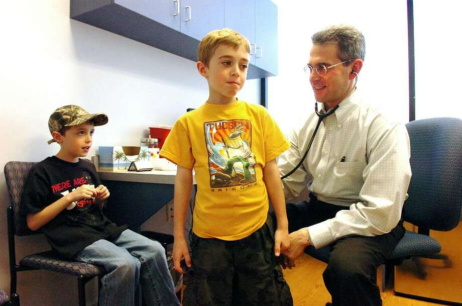 Dr. Kenneth Backman, an allergist associated with Bridgeport Hospital, examines Zachary Corsi, centern and Andrew Corsi, 7 year-old twins, at his practice Allergy and Asthma Care of Fairfield County in Fairfield, Conn., Thursday afternoon, April 8, 2010. Photo: Keelin Daly / Stamford Advocate