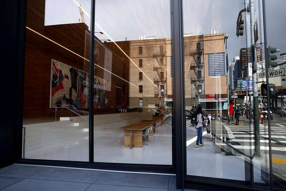 Brick buildings that neighbor the new tower at 222 Second St. are seen in the reflection of the glass partially enclosing the public space in the building in downtown San Francisco, California, on Monday, March 28, 2016.