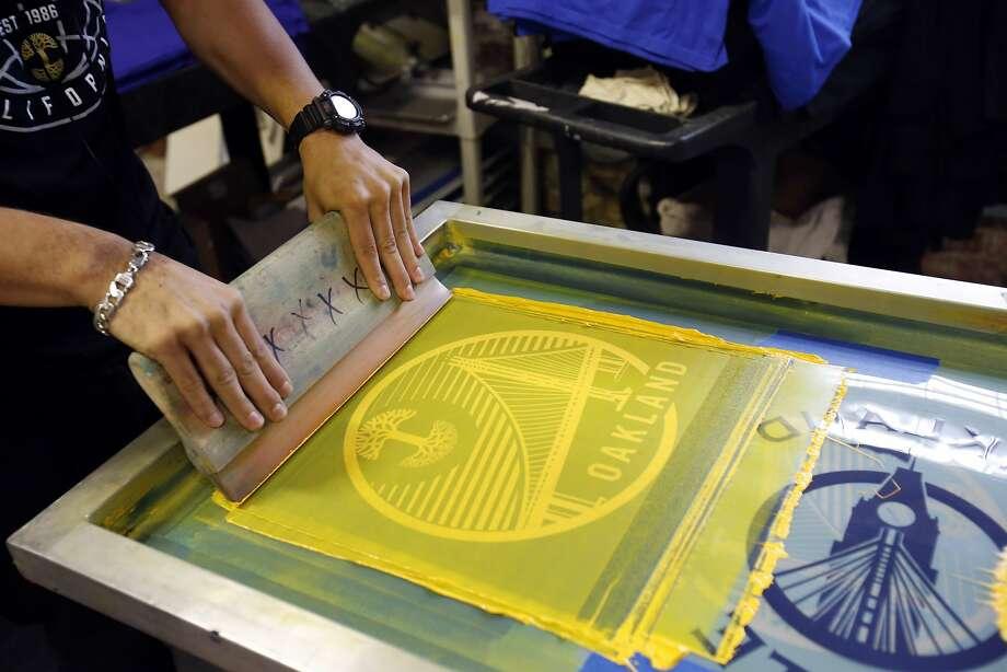 Jotzan Gonzalez presses paint onto a shirt as he screen prints shirts at Oaklandish in Oakland. Photo: Kathleen Duncan, The Chronicle