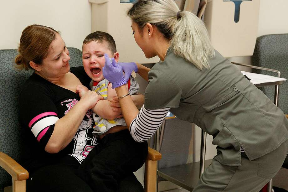 Elsa Sandoval-Anguiano from East Palo Alto comforts her son Damian Anguiano (middle), 4 years old, while he receives the MMRV-measles, mumps , rubella, varicella-- vaccine at the Kaiser pediatric immunization clinic in Redwood City, Calif., on Friday, January 23, 2015.  Photo: Liz Hafalia, The Chronicle