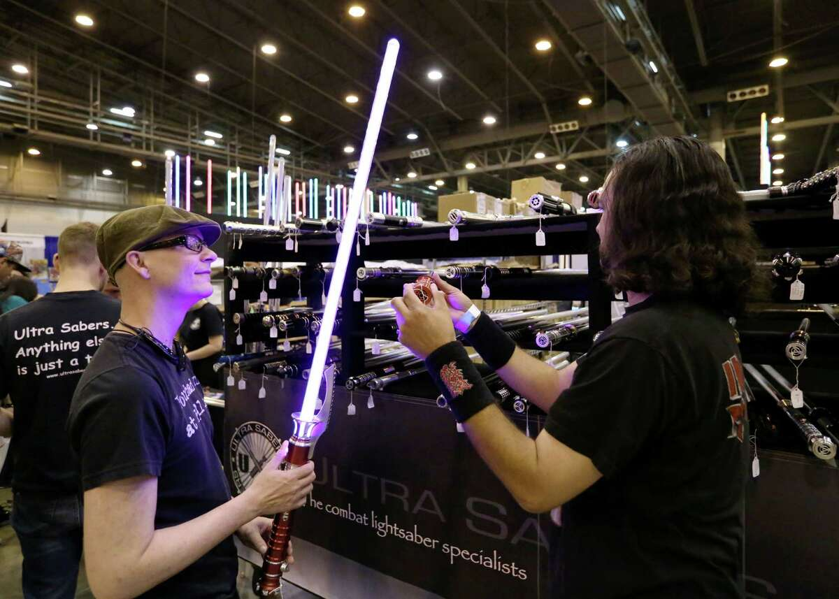 """Ron Loupe, left, checks out a light saber with his friend Freddy Flores at the 2015 Space City Comic Con at NRG Center Friday, July 24, 2015, in Houston. """"I just like cool light-up stuff,"""" Loupe said. ( Jon Shapley / Houston Chronicle )"""