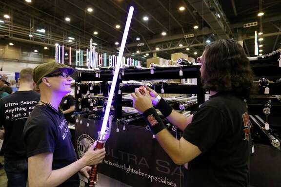 "Ron Loupe, left, checks out a light saber with his friend Freddy Flores at the 2015 Space City Comic Con at NRG Center Friday, July 24, 2015, in Houston.  ""I just like cool light-up stuff,"" Loupe said. ( Jon Shapley / Houston Chronicle )"
