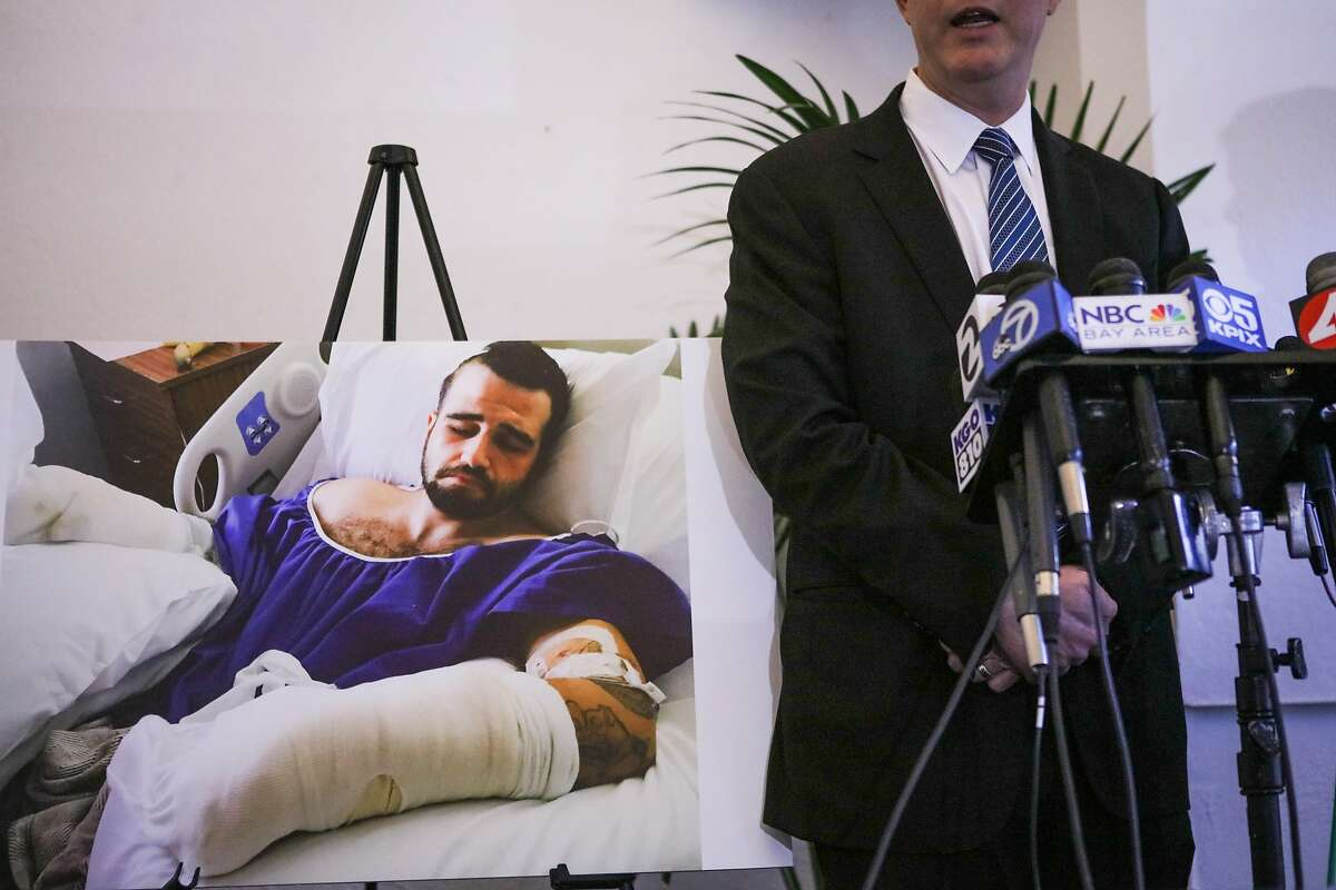 A poster of Stanislav Petrov, 29, in a hospital bed stands next to his lawyer Michael Haddad, while he speaks at a press conference, in Oakland, California, on Tuesday, March 29, 2016. Petrov was beaten in an alley on November 12, 2015 by Alameda County Sheriff deputies and his lawyers plan to file a federal civil rights lawsuit.