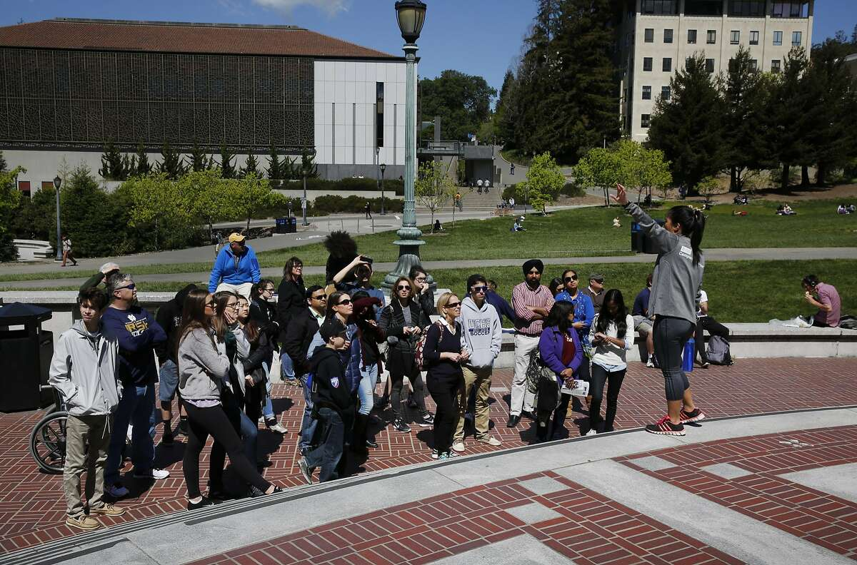 People listen to a guide during a campus tour for future students outside of University of California Library at University of California, Berkeley campus March 29, 2016 in Berkeley, Calif.