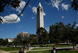 People walk past The Campanile at University of California, Berkeley campus March 29, 2016 in Berkeley, Calif.