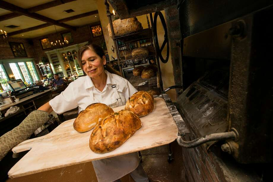 Colleen Lewis, co-owner of the Dancing Fox in Downtown Lodi pulls freshly baked loaves of garlic asiago bread from the brick fire oven. Photo: Dan Evans