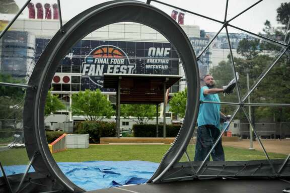 Mike Figiel cleans a dome being set up Tuesday for the NCAA Final Four Fan Fest at Discovery Green.
