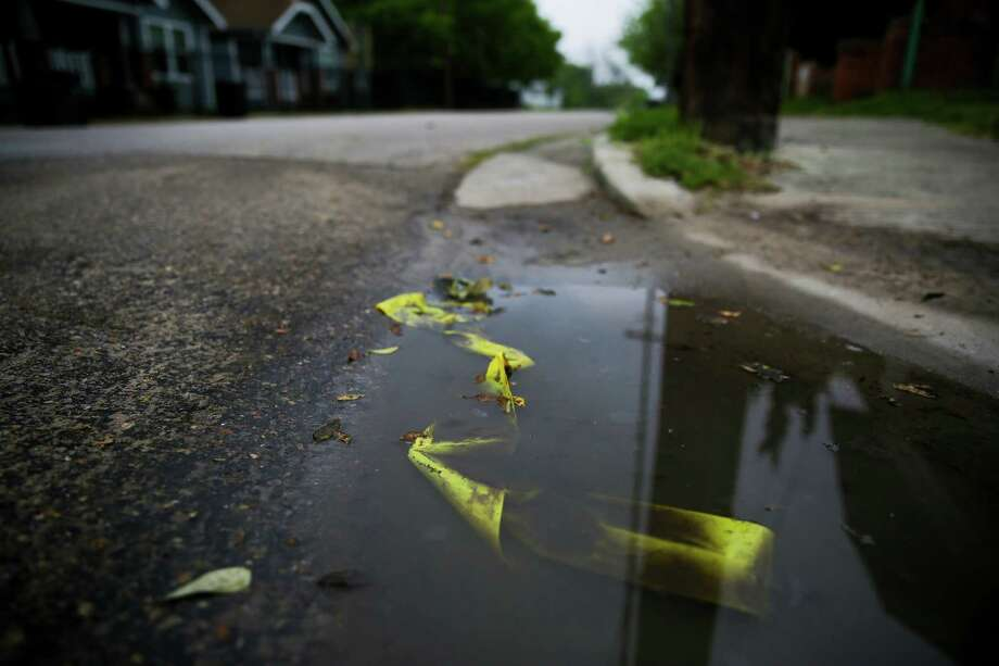 Police tape remains on Sampson Street in the Third Ward where two early morning drive-by shootings left a woman and a dog dead and a man injured Tuesday. Police did not yet know if the incidents were connected. Photo: Michael Ciaglo, Staff / © 2016  Houston Chronicle