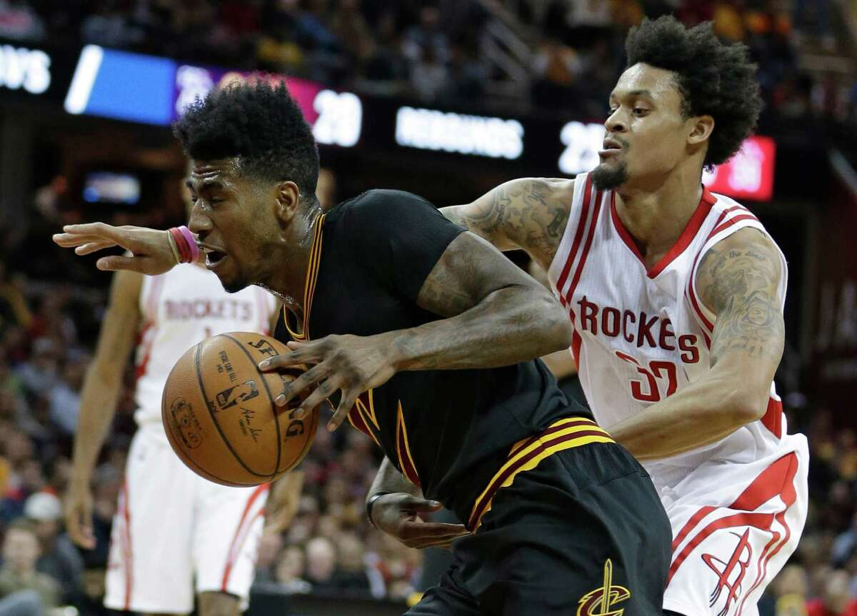 Cleveland Cavaliers' Iman Shumpert, left, drivers past Houston Rockets' K. J. McDaniels during the first half of an NBA basketball game Tuesday, March 29, 2016, in Cleveland.