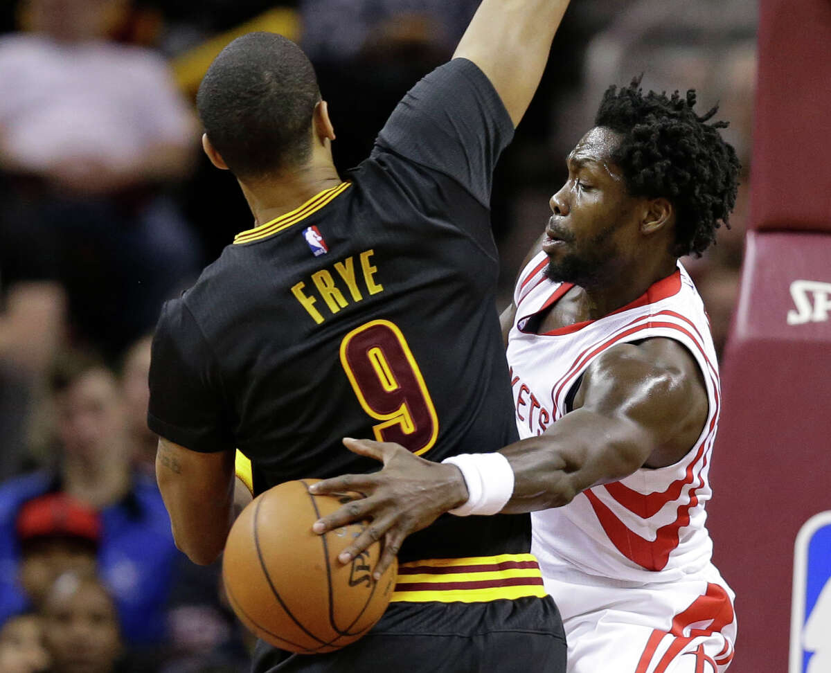 Houston Rockets' Patrick Beverley (2) passes around Cleveland Cavaliers' Channing Frye (9) during the first half of an NBA basketball game Tuesday, March 29, 2016, in Cleveland.