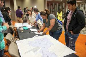 Sandra Estrada, center, and her son Ethan Estrada, right, a sophomore at South San High School, sign into a community meeting for parents, community leaders and other members of the South San Antonio Independent School District at Palto Alto College in San Antonio, Texas on Tuesday, March 29, 2016.