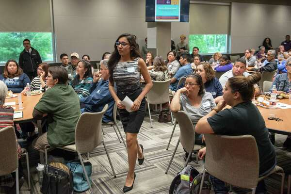 South San High School senior Araceli Garcia walks to the podium to speak during the packed community meeting for parents, community leaders and other members of the South San Antonio Independent School District at Palto Alto College.