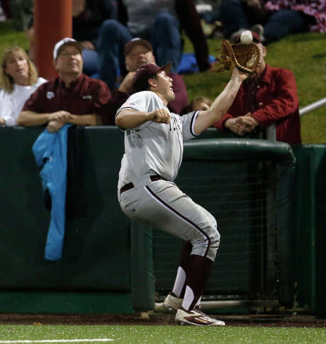 A&M first baseman Hunter Melton gives the Aggies fans along the fence a close-up view of his catch of a popup by UH's Joe Davis. Photo: Karen Warren, Staff / © 2016  Houston Chronicle