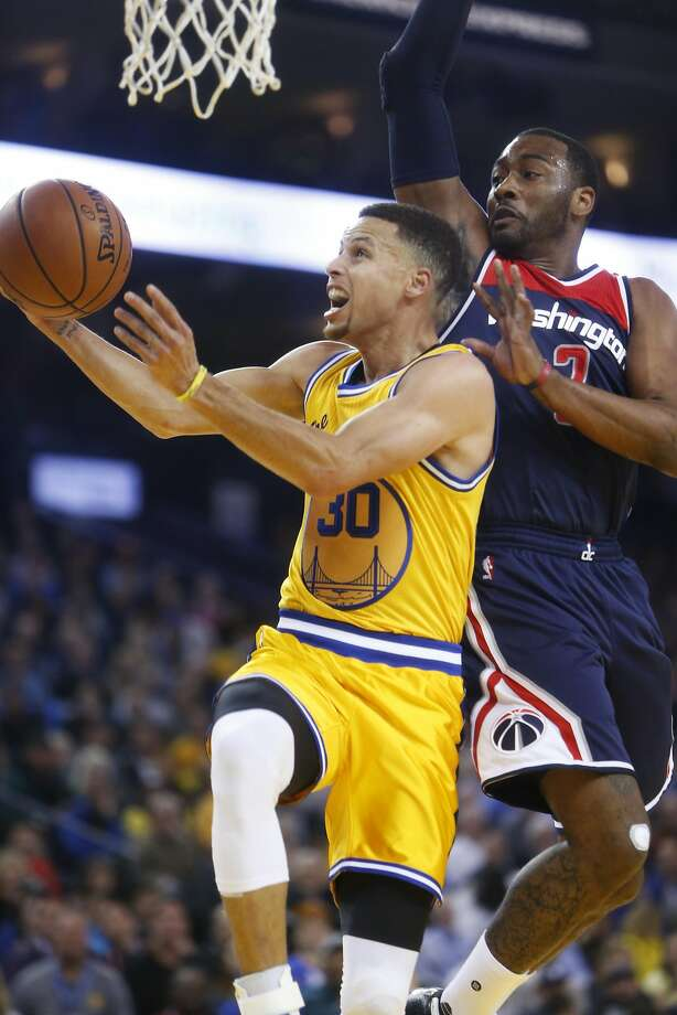 Golden State Warriors' Stephen Curry drives to the basket against Washington Wizards' John Wall in 1st quarter during NBA game at Oracle Arena in Oakland, Calif., on Tuesday, March 29, 2016. Photo: Scott Strazzante, The Chronicle