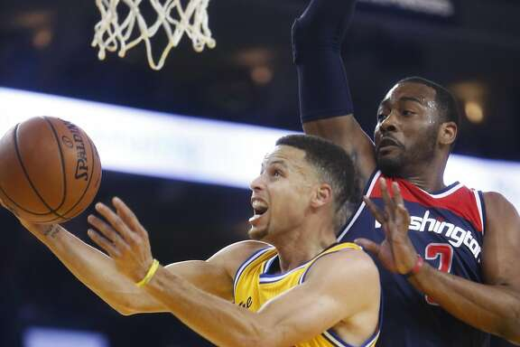 Golden State Warriors' Stephen Curry drives to the basket against Washington Wizards' John Wall in 1st quarter during NBA game at Oracle Arena in Oakland, Calif., on Tuesday, March 29, 2016.