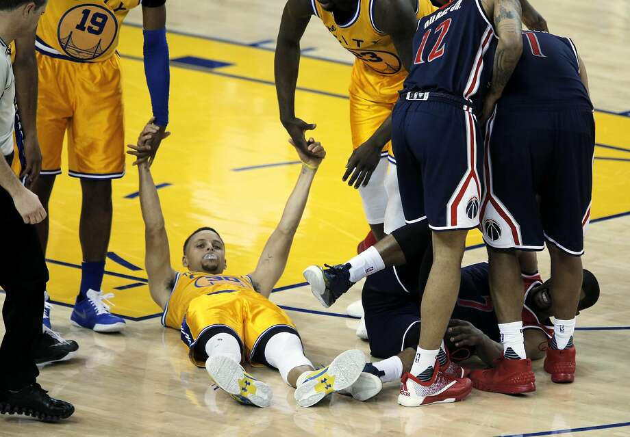 Stephen Curry (30) is helped up off the floor after a collision with Ramon Sessions (7) during the second half of the Golden State Warriors game against the Washington Wizards at Oracle Arena in Oakland, Calif., on Tuesday, March 29, 2016. Photo: Carlos Avila Gonzalez, The Chronicle