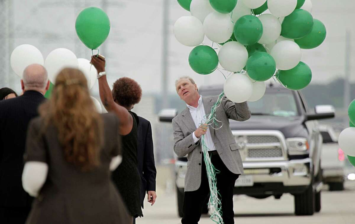 Dana Cote right, passes balloons to release during the Texas Department of Transportation ribbon cutting celebration for the completion of the newest segment of the Grand Parkway from Interstate 45 to U.S. 59 on March 29 in Spring.