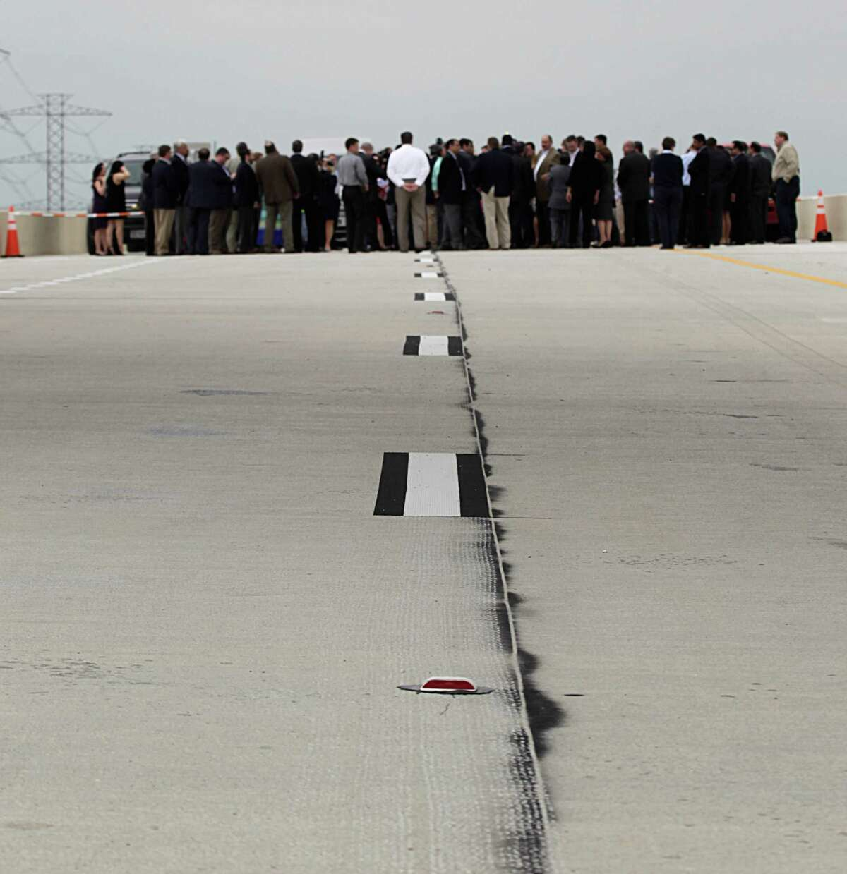 Officials and others guest stand on the Grand Parkway during the Texas Department of Transportation ribbon cutting celebration for the completion of the newest segment from Interstate 45 to U.S. 59 on March 29 in Spring.