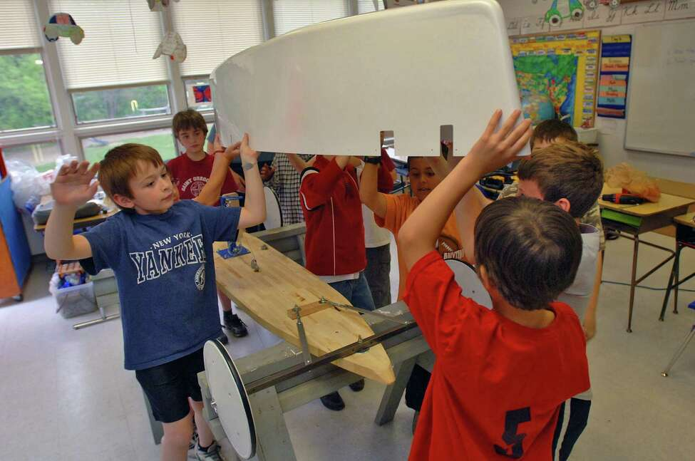 Students at St. Gregory's School in Loudonville, NY, work on a soap box derby car with teacher Beth Gregory after school on Tuesday May 9, 2006. (Philip Kamrass/Times Union)