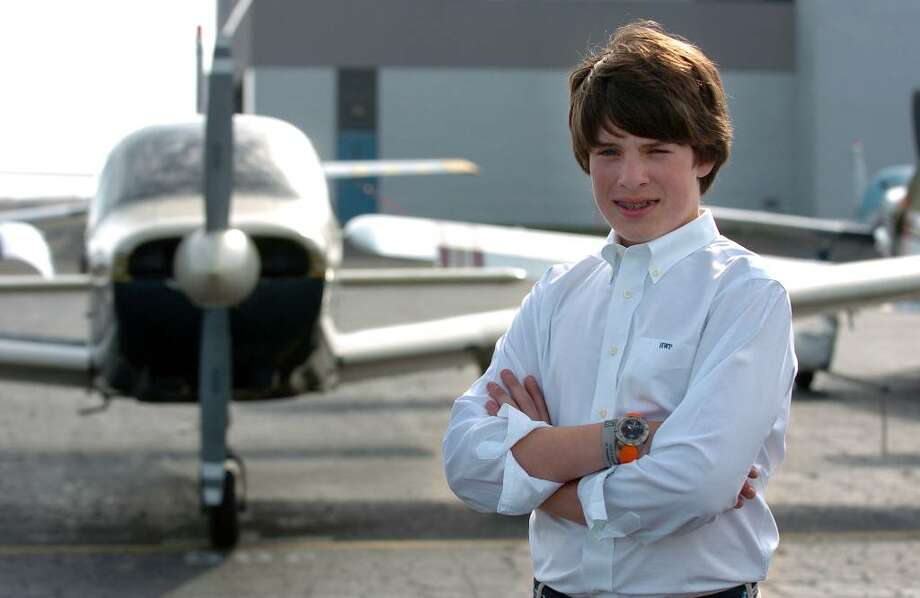 Harrison Paige, 12, has earned enough hours for his pilot's license, but will have to wait until he is 16 to get it. Until then, he will be a copilot on flights for medical patients, sponsored by a group called PALS. Here, Paige poses in front of the Piper Archer low wing plane that he flies in on weekends, at Three Wing Flight School at Sikorsky Airport in Stratford, Conn. on Thursday April 08, 2010. Photo: Christian Abraham / Connecticut Post