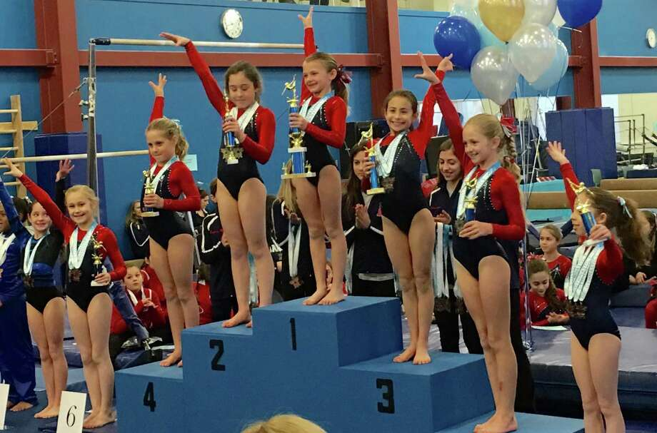 Darien Level 3 gymnasts topping the podium in the age eight All Around were from left, Lindy Mueller, Penelope Arredondo, Anna Altier, Ava Licata, Sydney Berk, Annelise Enters and Sophia Gaffer Photo: Contributed / Darien News