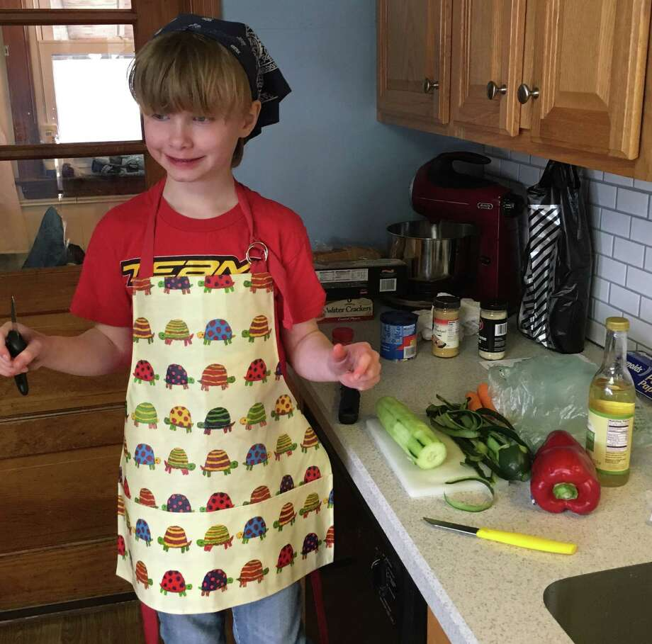 Matilda Gish, 7, works on a dinner party for her mother's birthday. She and her mom, Times Union features editor Jennifer Gish, have used cooking as a way to help address issues that come up as a result of Matilda having autism spectrum disorder. (Jennifer Gish)