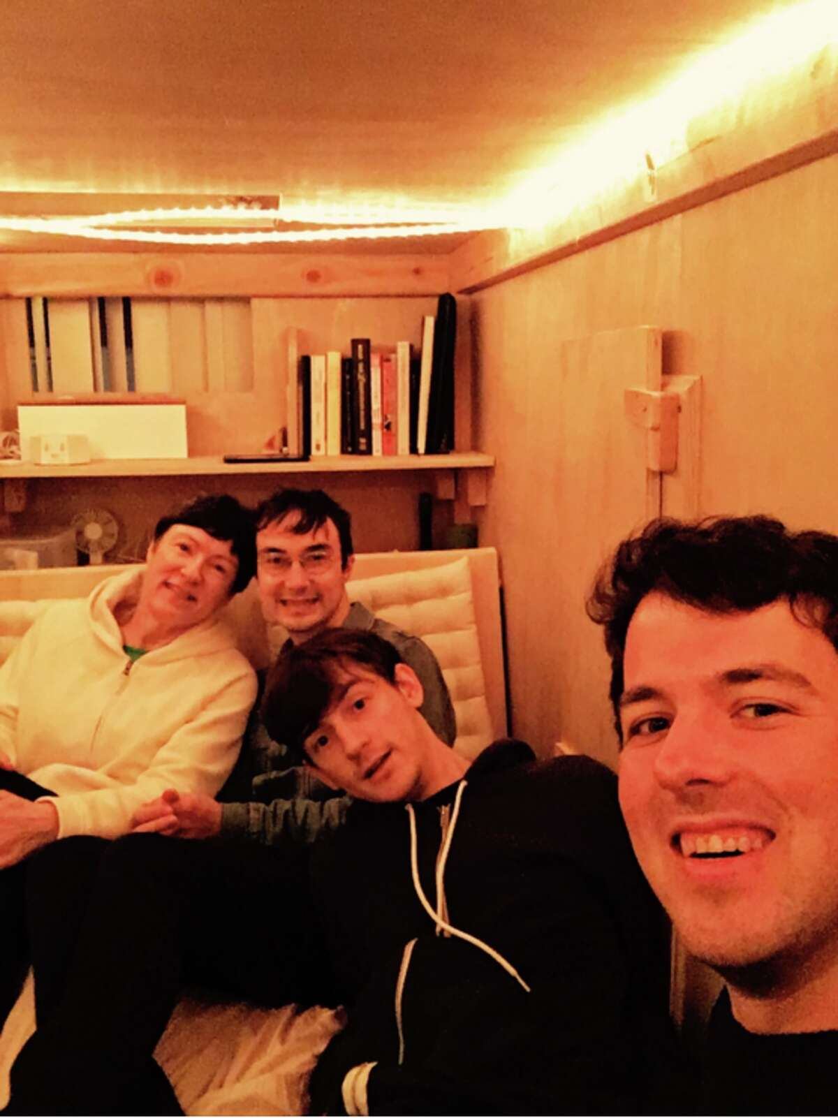 San Francisco resident Peter Berkowitz lives in a box in a friend's living room and pays only $400 a month for rent. Peter is pictured right in this group photo.