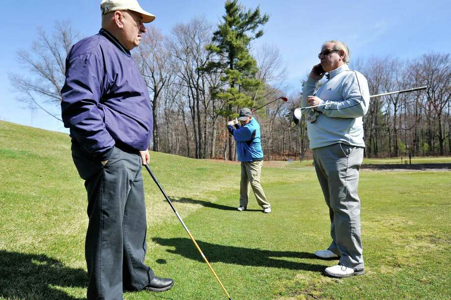 Schenectady friends, Joe Melideo, left,  looks on as Gary Costanzo, right, calls a mutual friend as they try to find a fourth person to golf with them and Mike Brennan, background, at the Schenectady Municipal Golf Course on Wednesday, March 30, 2016, in Schenectady, N.Y.  The course is now open for the season.   (Paul Buckowski / Times Union) Photo: PAUL BUCKOWSKI / 10036006A