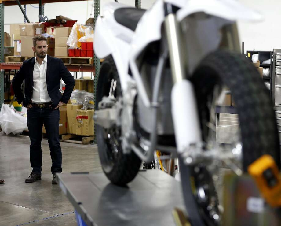 CEO Marc Fenigstein stands beside one of the electric motorcycles in the research and development area at Alta Motors in Brisbane. Photo: Connor Radnovich, The Chronicle