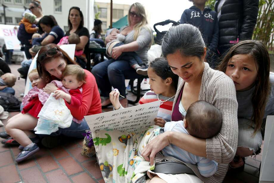 Mildred Musni (right) breast feeds her son Eliseo and is joined by other mothers in protest at the main entrance of the city Human Services Agency in San Francisco, Calif. on Wednesday, March 30, 2016 after Musni was forced to cover up by a security guard when she attempted to feed Eliseo inside the facility a few months ago. With Musni are her older daughter Sentia (left) and step-daughter Vanessa Trujillo (right). Photo: Paul Chinn, The Chronicle