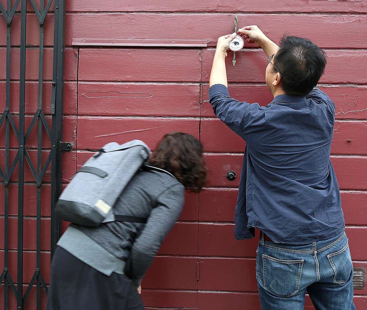 Curator Sarah Klein (left) and David Kwan (right) work on changing the films showing at Peephole Cinema, a public art installation on Orange Alley in San Francisco, California, on wednesday, march 30, 2016.