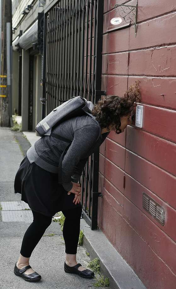 Curator Sarah Klein checks films showing at Peephole Cinema, a public art installation on Orange Alley in San Francisco, California, on wednesday, march 30, 2016. Photo: Liz Hafalia, The Chronicle