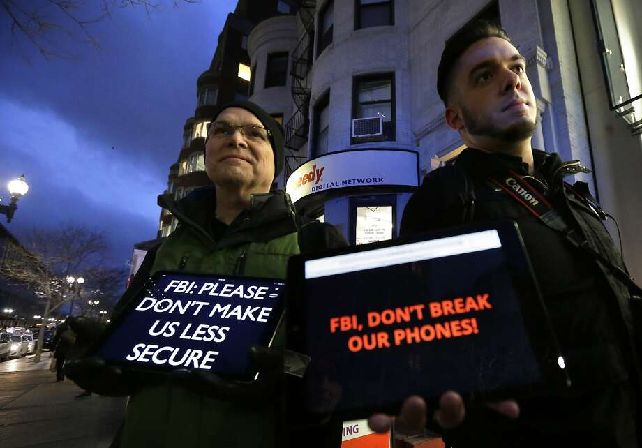 In this Feb. 23, 2016, file photo, demonstrators Peter Brockmann, of Northborough, Mass., left, and Chris Gladney, of Boston, right, display iPads with messages on their screens outside an Apple store in Boston. Photo: Steven Senne, AP
