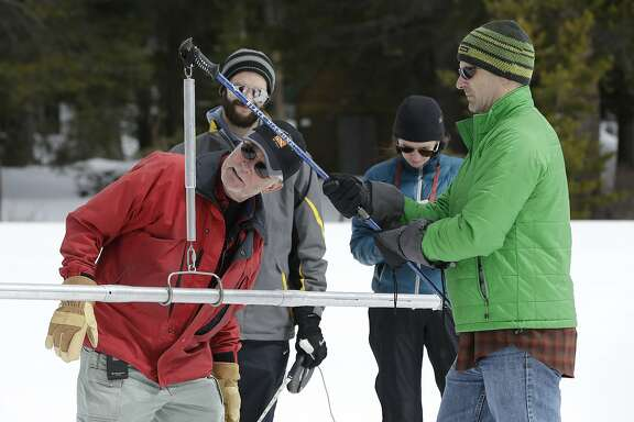 Frank Gehrke, chief of the California Cooperative Snow Surveys Program for the Department of Water Resources, checks the weight of the snowpack, on a scale held by Dan Brumbaugh, right, as he performs the snow survey at Phillips Station, Wednesday, March 30, 2016, in Echo Summit, Calif. The survey showed the snowpack at about 95 percent of normal for this site at this time of year. Brumbaugh, John Thompson, second from left, and Sarah Carvill, third from left, are Policy Fellows from the California Council on Science and Technology. (AP Photo/Rich Pedroncelli)