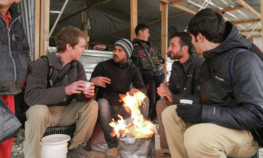 Westport-native Chris Temple, left, and fellow filmmaker Zach Ingrasci, far right, discuss life at Za'tari camp with their Syrian refugee neighbors. Photo: Courtesy Of 1001 Media /Living On One / Contributed Photo / Connecticut Post contributed