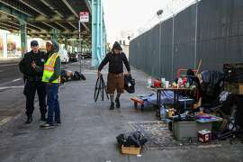 Larry Muraoka, a homeless man packs up his belongings as police and a Department of Public Works employee assess the situation, on Division Street, in San Francisco, California, on Tuesday, March 2, 2016.